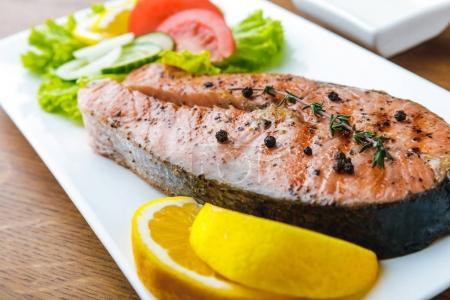 close-up view of delicious grilled salmon with lemon slices and vegetable salad