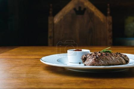 delicious grilled steak with rosemary and bbq sauce on plate on wooden table