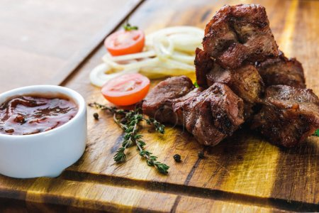 Photo for Delicious grilled meat with vegetables and bbq sauce on wooden board - Royalty Free Image