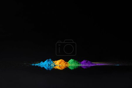 Photo for Four colors of holi powder for Hindu spring festival, on black with reflection - Royalty Free Image