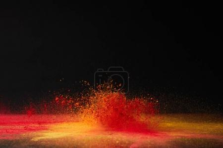 orange holi powder explosion on black, Hindu spring festival