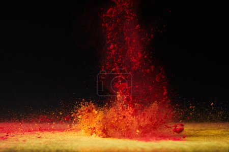 Photo for Orange holi powder explosion on black, Hindu spring festival - Royalty Free Image