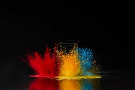 Photo for Red, blue and yellow holi powder explosion on black, Hindu spring festival - Royalty Free Image