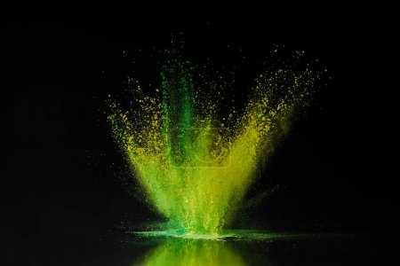 Photo for Green and yellow holi powder explosion on black, traditional Indian festival of colours - Royalty Free Image