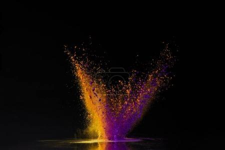explosion de poudre holi orange et violet sur le festival du printemps noir, hindou