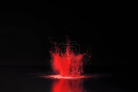 red holi powder explosion on black, traditional Indian festival of colours