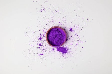 top view of purple holi paint in bowl isolated on white, festival of colours