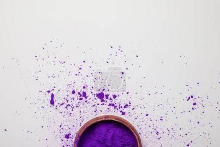 top view of purple holi paint in bowl isolated on white, Hindu spring festival