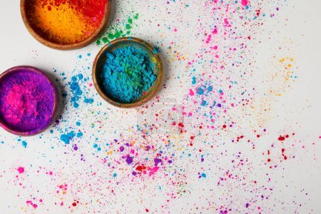 top view of traditional holi paint in bowls isolated on white, Hindu spring festival of colours