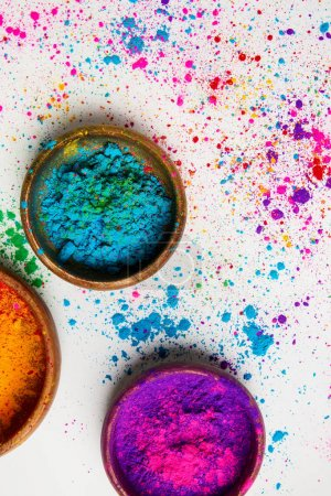 top view of colorful holi powder in bowls isolated on white