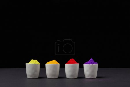 row of colorful holi paint in four bowls on black, Hindu spring festival