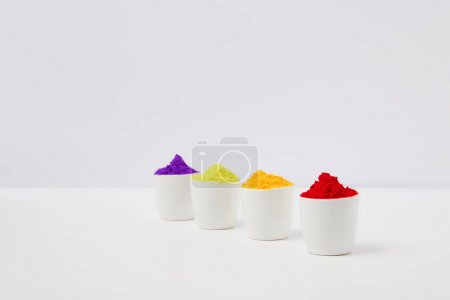Photo for Row of colorful holi paint in bowls on white, Hindu spring festival - Royalty Free Image