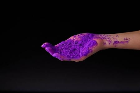 cropped view of hand with purple holi powder, isolated on black