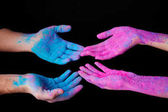 cropped view of couple with pink and blue holi paint on hands, isolated on black