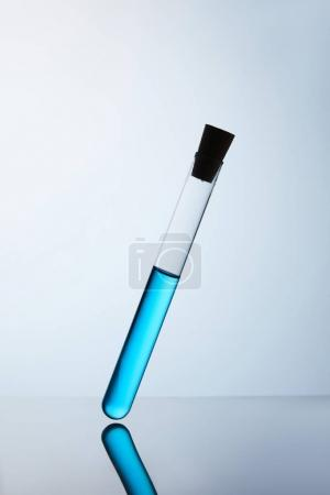 chemistry tube filled with blue liquid on reflective surface