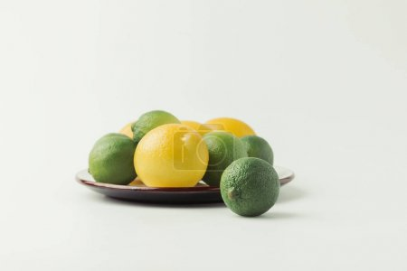 Lemons and limes on plate isolated on white background