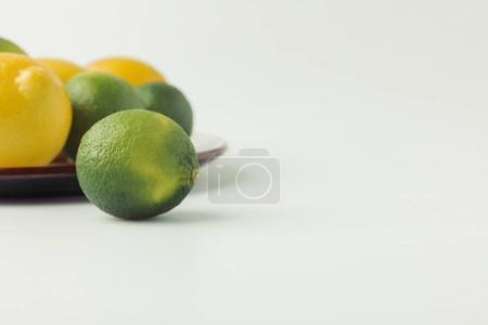 Photo pour Limes vertes et citrons sur plaque sur fond blanc - image libre de droit