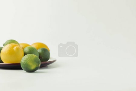 Green and Key limes on plate on white background