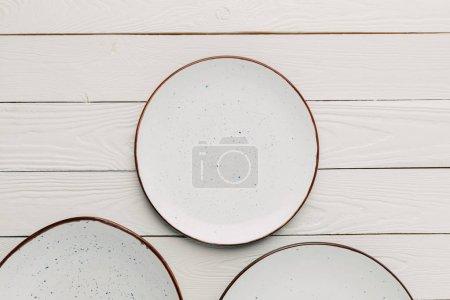 Empty ceramic plates on white wooden background
