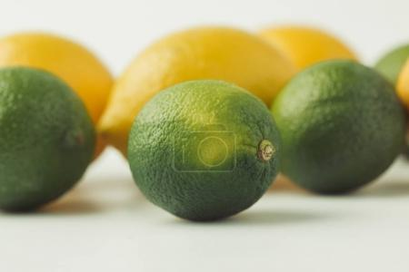 Raw limes and lemons isolated on white background