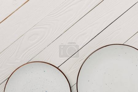 Empty glazed plates on white wooden background