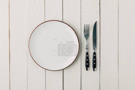 Photo for Empty plate and cutlery on white wooden background - Royalty Free Image