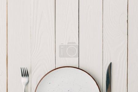 Empty plate with fork and knife on white wooden background