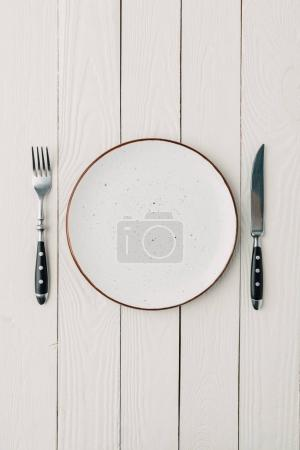 Photo for Top view of plate and cutlery on white wooden background - Royalty Free Image