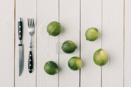 top view of cutlery and green limes on white wooden background