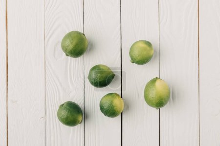 Greek limes on white wooden background