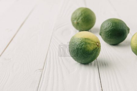 Raw green limes on white wooden background