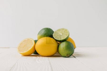 Lemons and limes on white wooden background