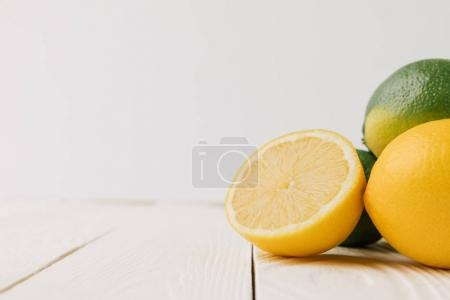 Ripe citrus fruits on white wooden background