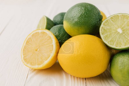 Green limes and yellow lemons on white wooden background