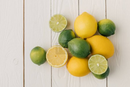 Juicy sour citruses on white wooden background