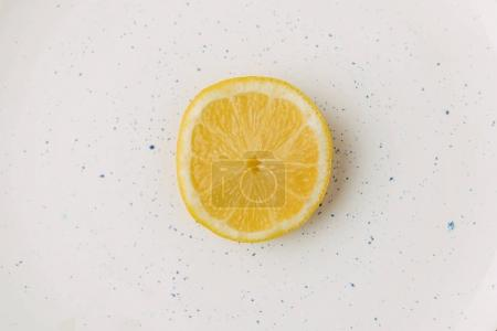 Half of juicy lemon on glazed plate
