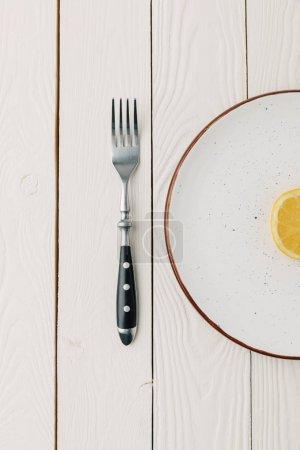Photo pour La moitié du citron juteux sur assiette avec fourchette sur fond blanc en bois - image libre de droit