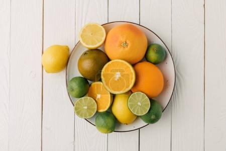 Juicy sour citruses on plate on white wooden background