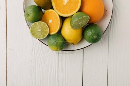 Citrus fruits on plate on white wooden background