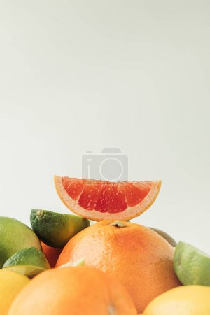 Grapefruit slice on top of citrus fruits isolated on white background