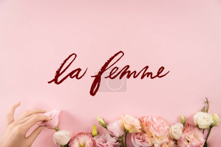 Photo for Top view of hand arranging beautiful tender flowers with LE FEMME sign isolated on pink background - Royalty Free Image