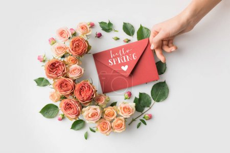 hand holding envelope with HELLO SPRING lettering surrounded by beautiful pink flowers isolated on white