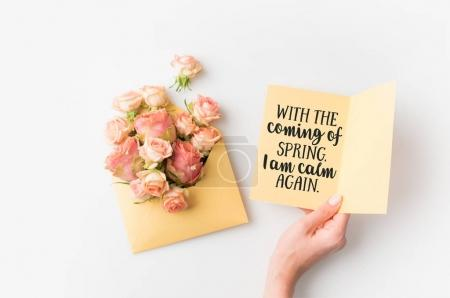 hand holding paper with spring quote beside pink flowers in envelope isolated on white