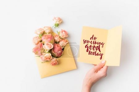 Photo for Hand holding paper with DO SOMETHING GOOD TODAY inscription beside pink flowers in envelope isolated on white - Royalty Free Image