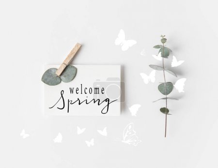 Photo for Flat lay with eucalyptus and WELCOME SPRING sign on paper on white surface - Royalty Free Image