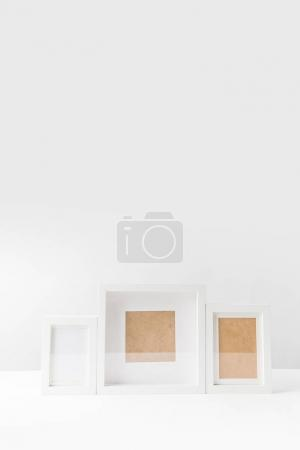 various empty white photo frames on white