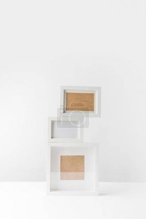 empty white photo frames stacked on white