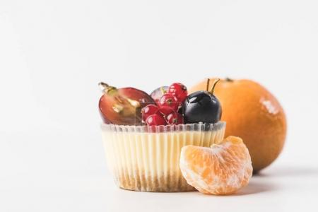 close up view of sweet cupcake with berries, fruits and tangerine near by isolated on white