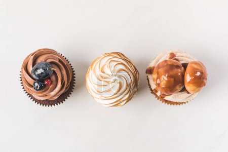 top view of arrangement of tasty cupcakes isolated on white