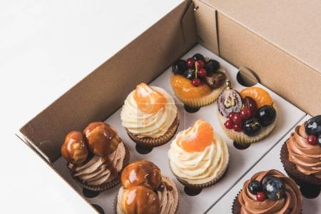 Photo for Close up view of various types of cupcakes in cardboard box isolated on white - Royalty Free Image